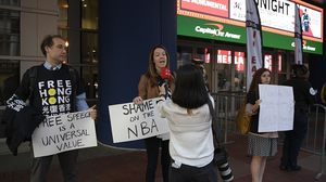 AP通信109ワシントンでActivists hold signs outside Capital One Arena before an NBA preseason basketball game between the Washington Wizards and the Guangzhou Loong-Lions.jpg